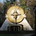 """Ołtarz Papieski - Sopot - 1999. Twórcą ołtarza był prof. Marian Kołodziej. Ołtarz w swej głównej części przedstawia rozpiętego na krzyżu CHRYSTUSA i podtrzymującego GO BOGA OJCA. Nawiązuje tym samym do średniowiecznego wyobrażenia TRÓJCY ŚWIĘTEJ nazywanego TRONEM ŁASKI oraz do przesłania pielgrzymki Jana Pawła II: """"BÓG JEST MIŁOŚCIĄ!"""" Pomysł plastyczny ołtarza oparty jest na trzech zasadniczych elementach: krzyżu, pierwszym i podstawowym symbolu wiary; trójkącie, wyobrażającym OKO OPATRZNOŚCI i okręgu, który tutaj może przestawiać monstrancję. Zarówno trójkąt, jak i okrąg - figury doskonałe - były w tradycji i są symbolami BOGA, absolutu."""